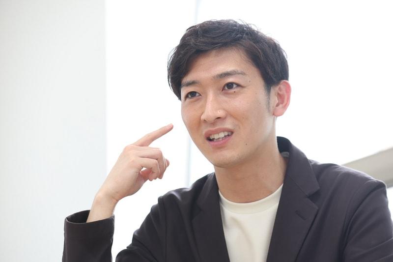 右手で指さす小林正寿さん