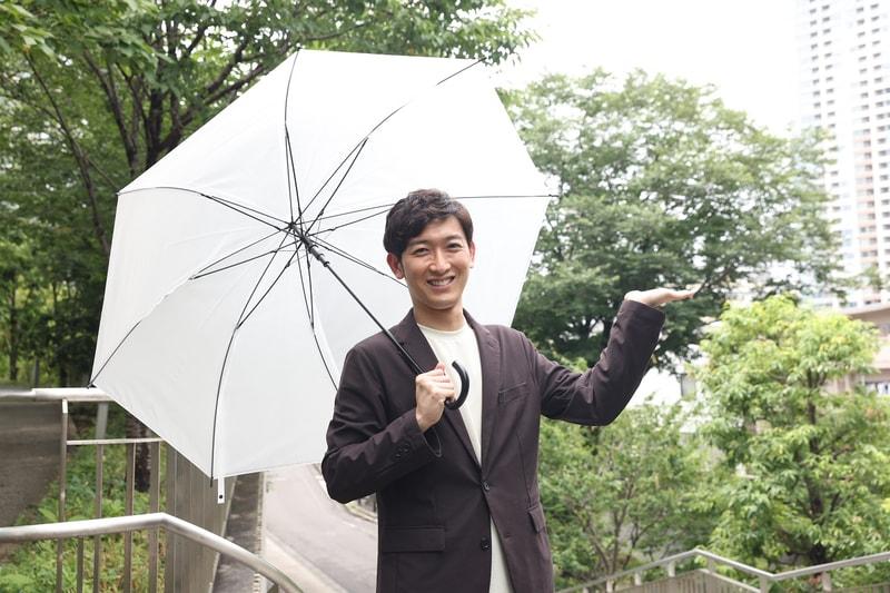 傘を持つ小林正寿さん
